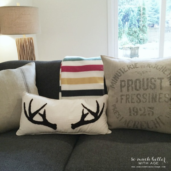 A grey couch with an antler pillow and striped throw blanket.