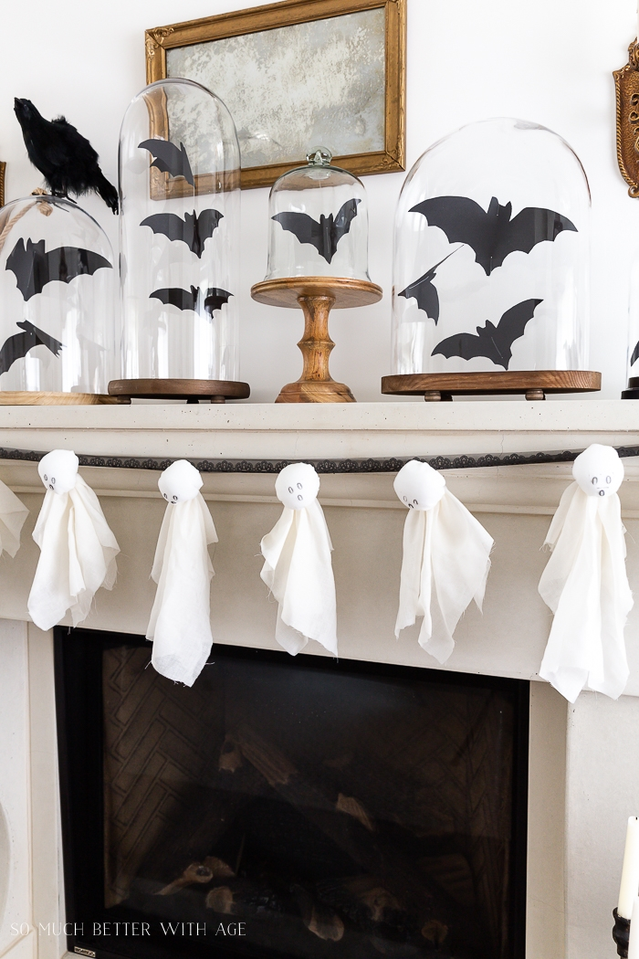 Bat in cloches with ghosts on mantel.