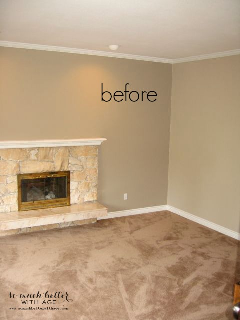 The peach stone fireplace in an empty room with a brass metal plate on it.