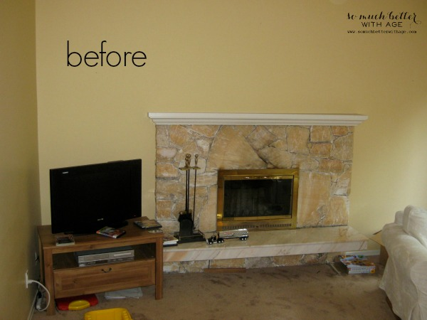 The peach granite fireplace with a small tv beside it.