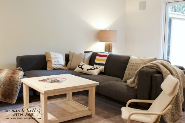 A grey sectional couch with a light wooden table and faux fur throw in the living room.