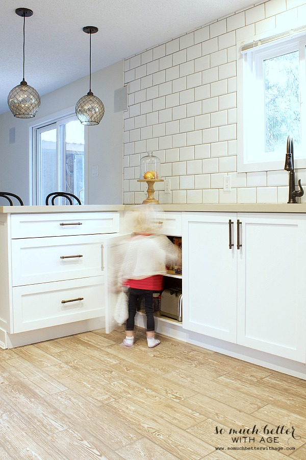 A little girl opening up the kitchen cabinet.