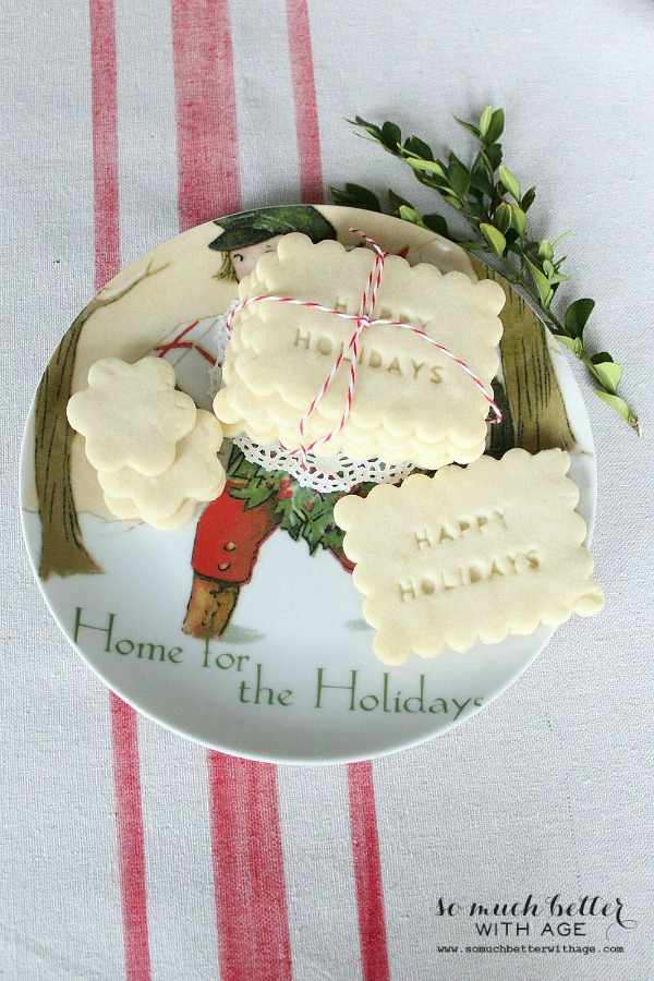 Shortbread cookies on a holiday plate with a sprig of greenery beside it.