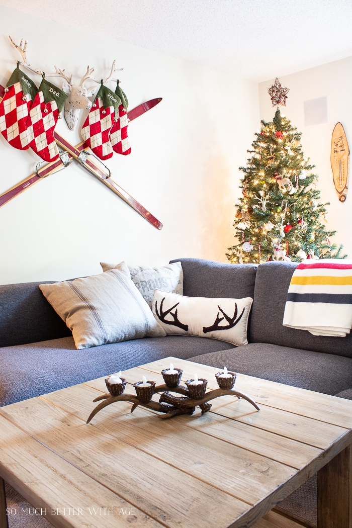 Skiis, a deer head with antlers, Christmas tree and stocking in the rustic cabin.