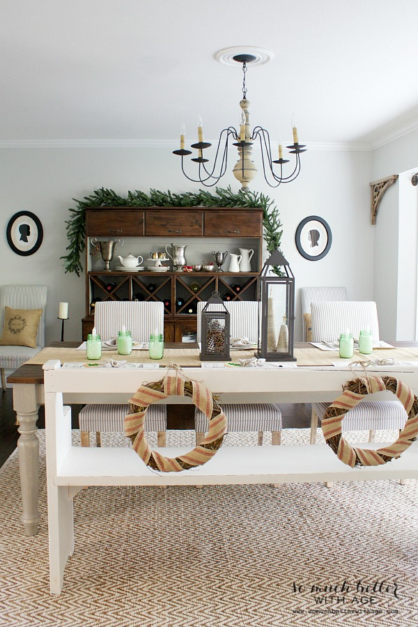 Christmas wreaths hanging on the back of white bench at dining table and open shelving behind table.