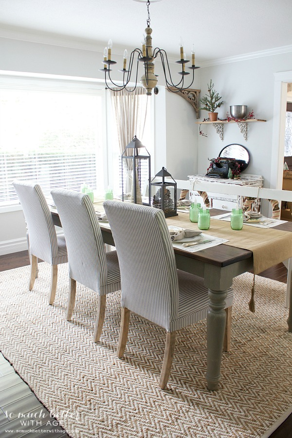 Dining room white and blue striped chairs, wooden chandelier, neutral table runner and candles on the table.