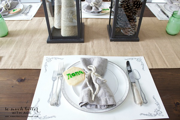 Table setting with sugar cookie monogramed with guest name in light green on plate.