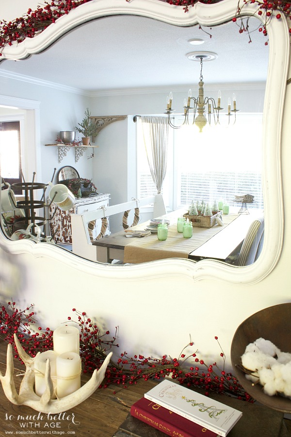 White mirror with berries around it in dining room.