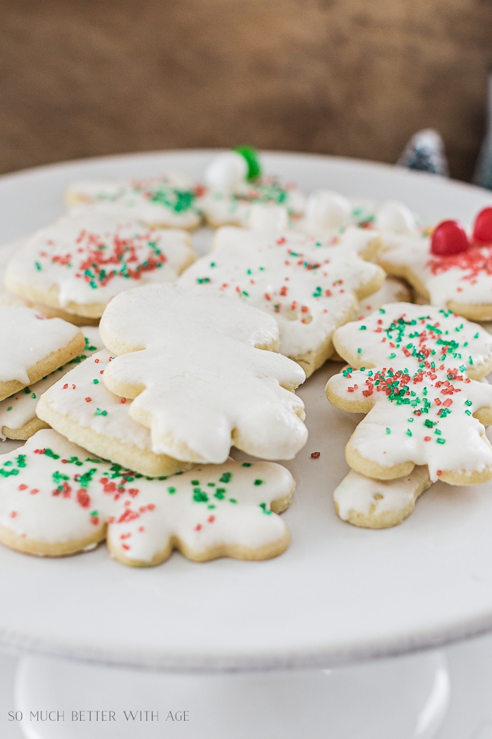 The iced sugar cookies on a cake stand with red and green sparkles on them.