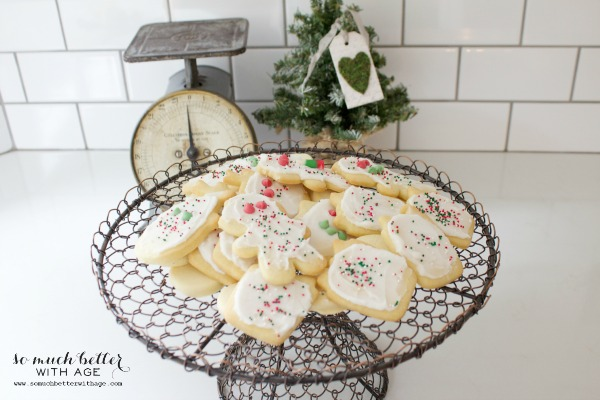 Sugar cookies on counter with scale and Christmas tree in background.