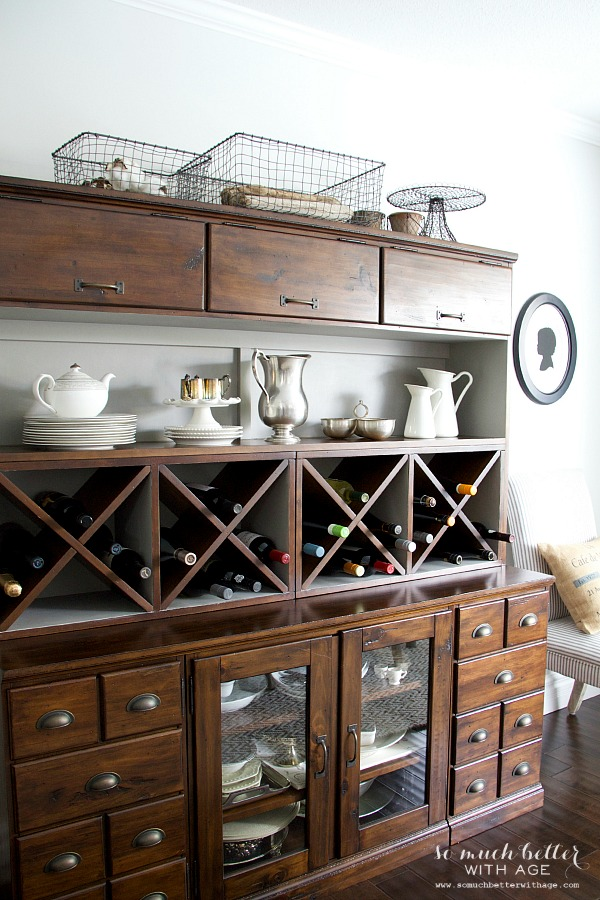 The cabinet with a grey color over the white on back behind the china.