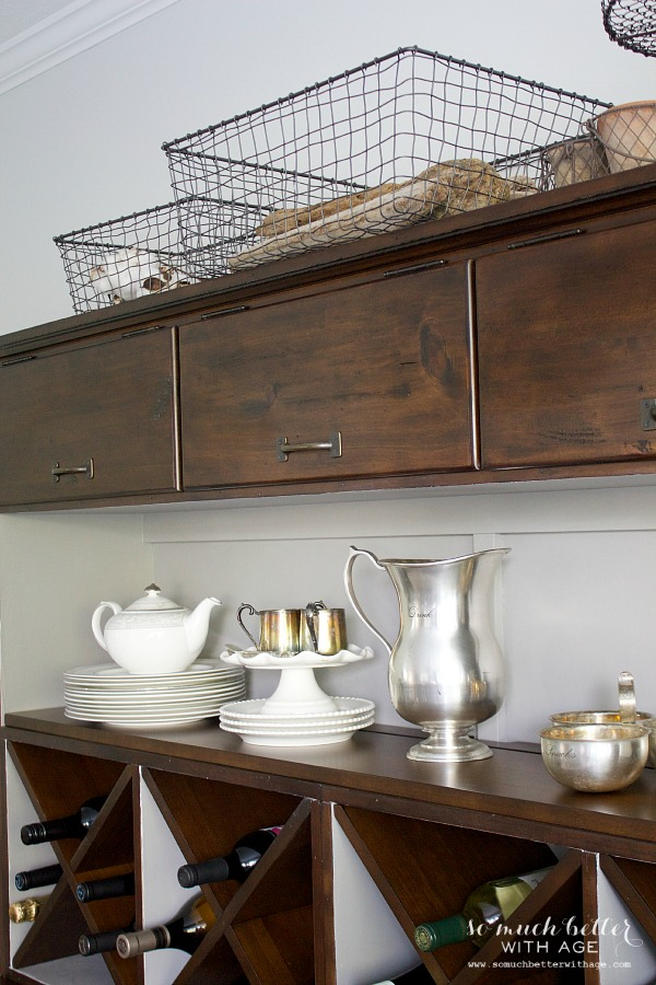 Brown cabinet with wire baskets on top.