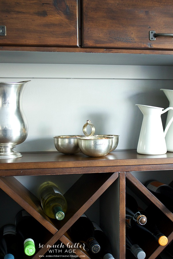Silver bowls on cabinet shelf.