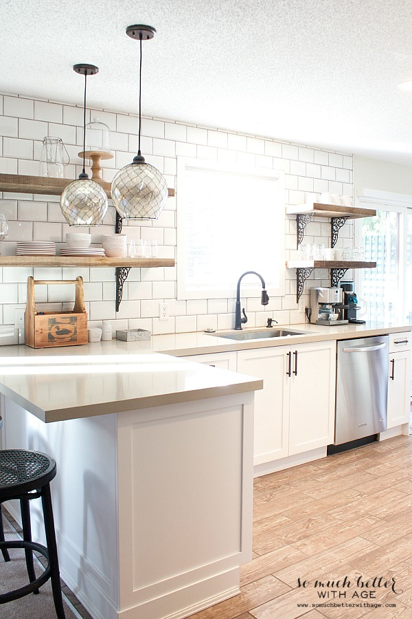 White kitchen with clear and black pendant lights and wood floor.