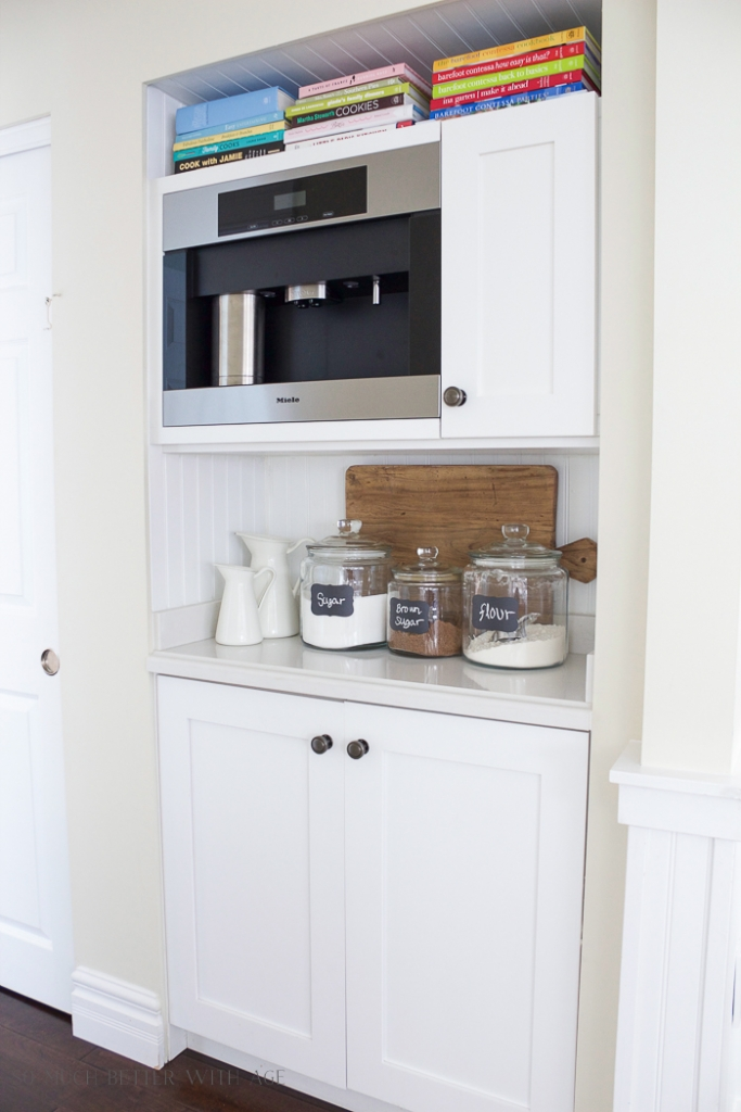 A white shelf with a coffee maker on it, and below is some clear glass jars with sugar, flour, and brown sugar on a white cabinet.