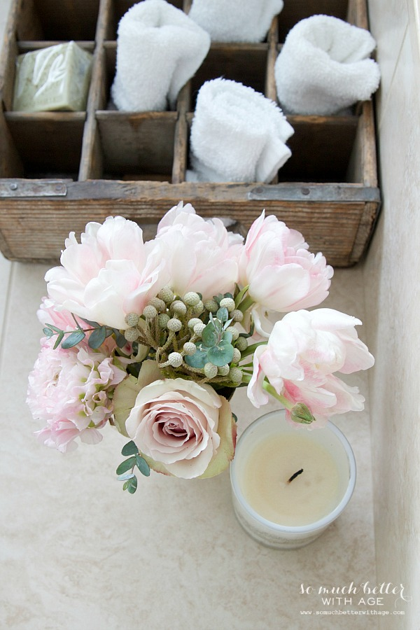 Candles and flowers and towels beside the tub.