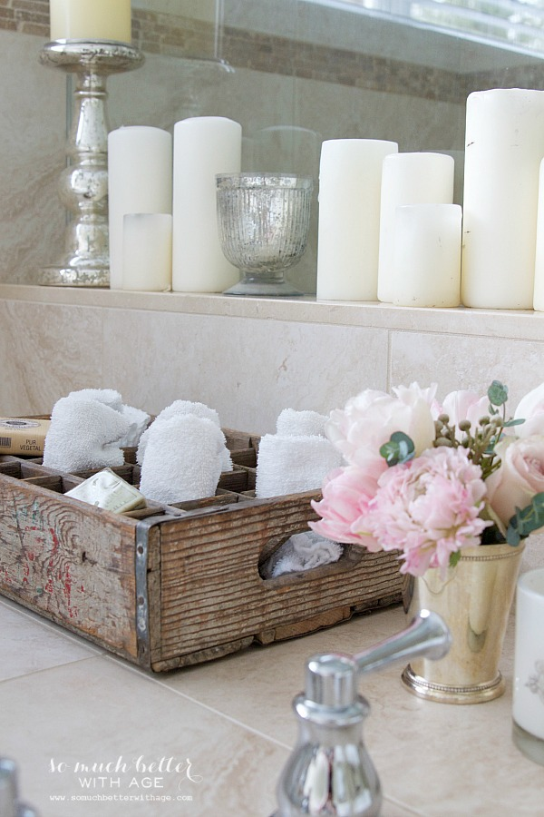 Vintage old crate with candles beside tub.