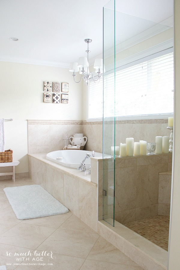 Soaker tub with chandelier above it.