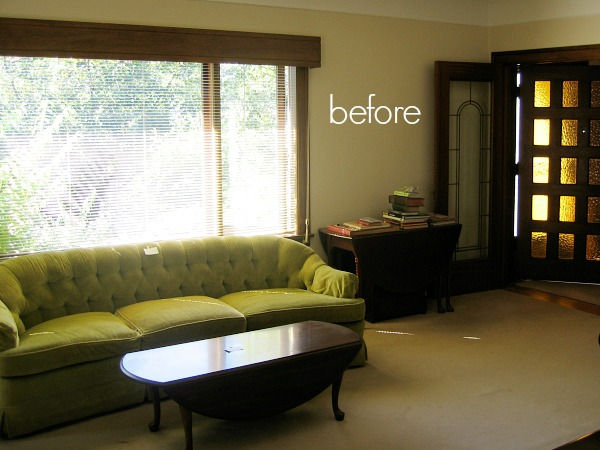 A green velvet couch in living room and wooden French doors.