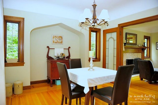 Simple dining room with wooden floors, a small table and updated light fixture above the table.
