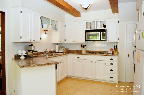 White cabinets in kitchen and wooden beams added.