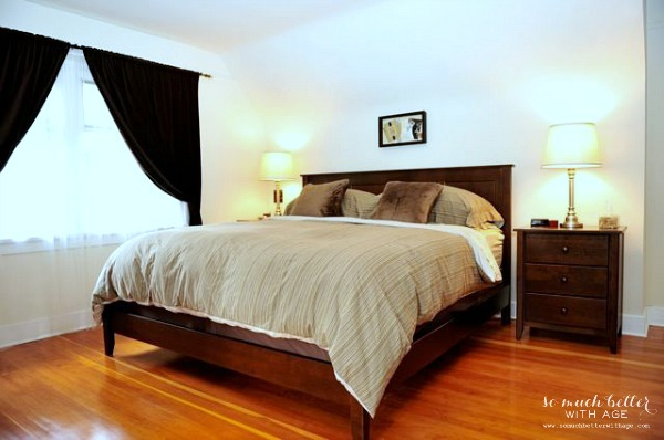 The master bedroom with wood floors, brown curtains and a wooden bed.