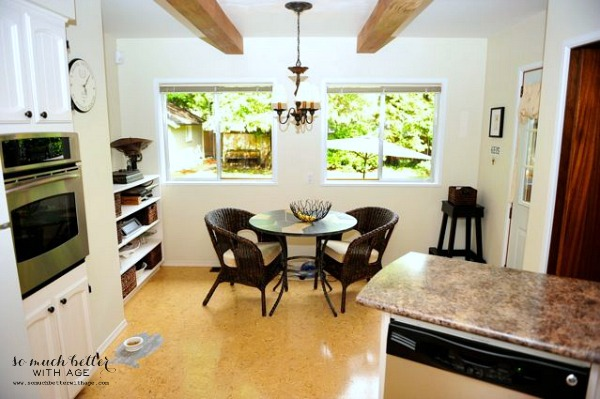 With kitchen with wood beams and a small table in front of kitchen window.