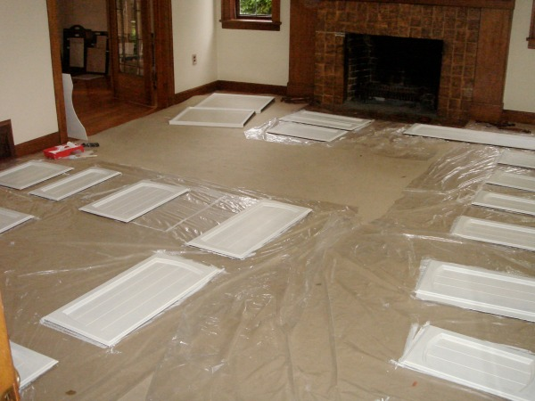 The cabinet doors laid down in the living room on plastic for painting white.