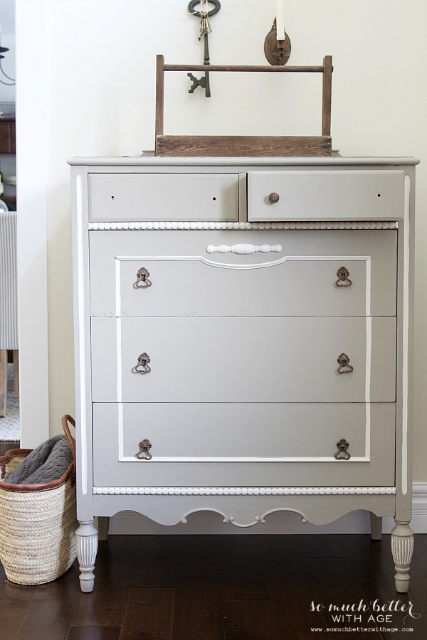Dresser with one drawer open painted a subtle white.