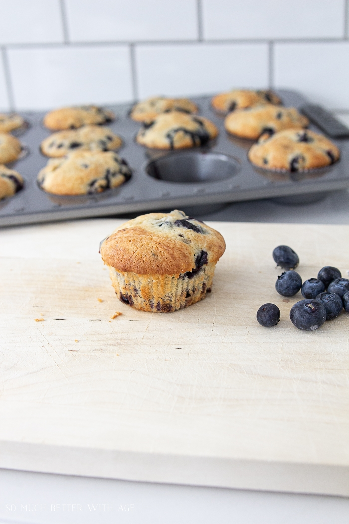 Blueberry muffins baked with one on the counter.