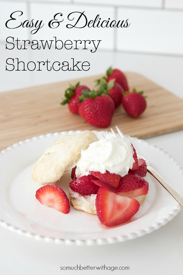 Plate full of strawberries and shortcake with more strawberries on cutting board.