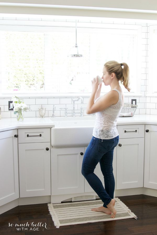 Girl with pony tail standing in white kitchen drinking from a coffee cup.