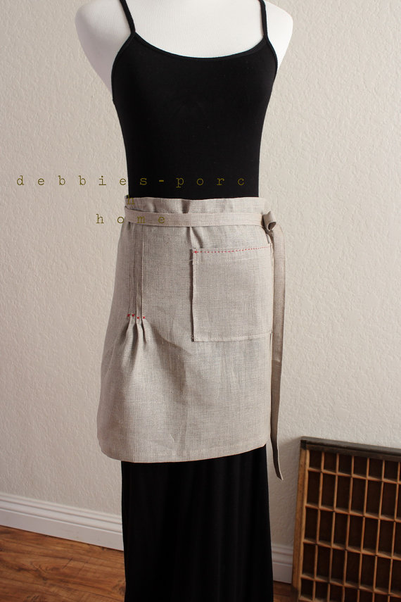 A linen apron with red stitching.