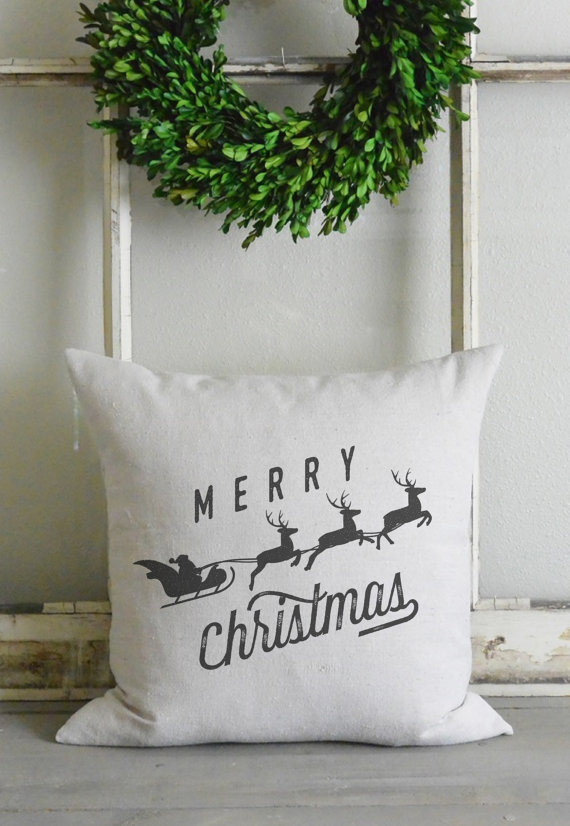 A Merry Christmas pillow with a sleigh an reindeer.