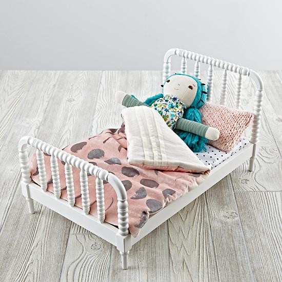 A little dolls bed with a small doll in the bed.