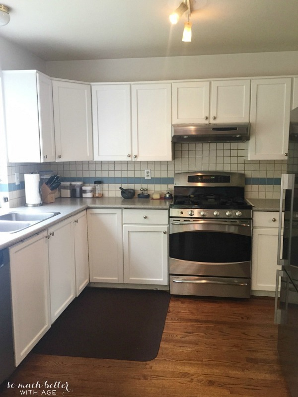 The kitchen with white cabinets and a stainless steel oven.