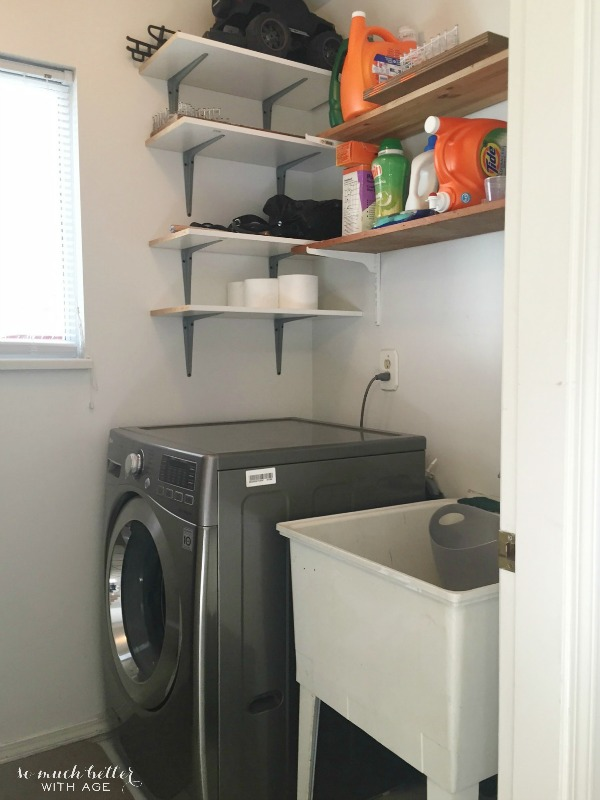 There is a washing machine and open shelves in the laundry room.