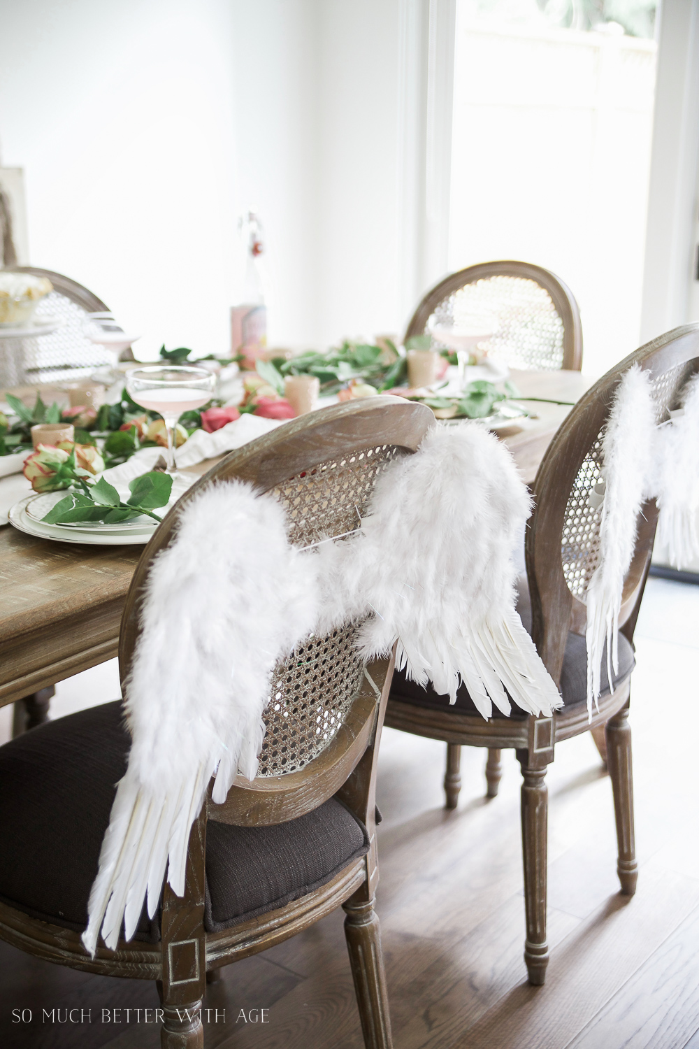 Pretty pink roses Valentine's Day table setting / angel wings on back of chair - So Much Better With Age