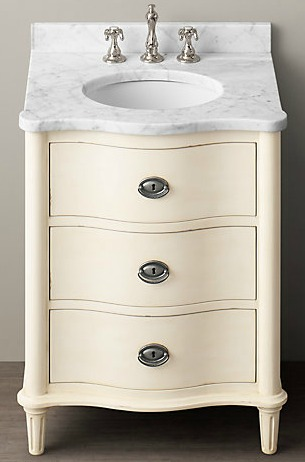 White vanity with silver faucet and silver handles.