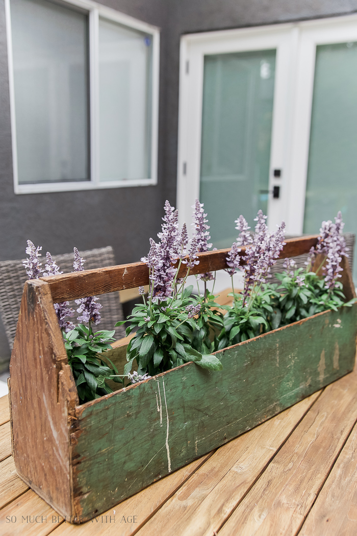 Wooden container on table outside on deck with flowers in it.