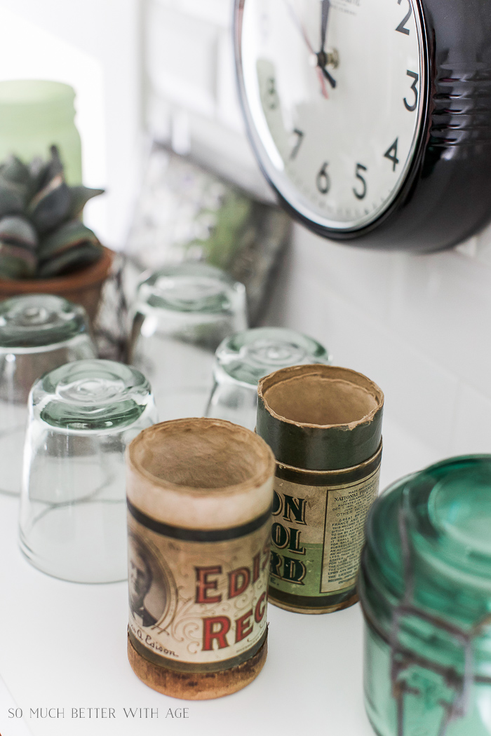 Cups and vintage containers on counter in kitchen.
