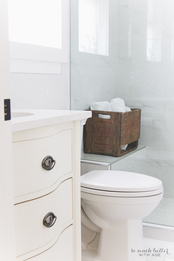 Vintage white bathroom using porcelain tile that looks like carrara marble