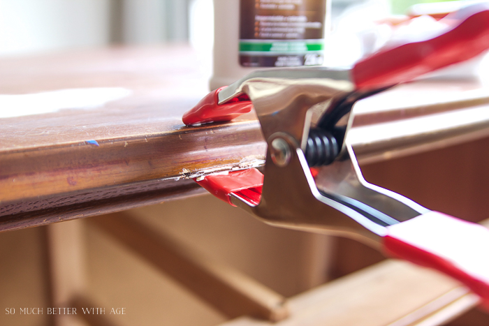 Clamp with wood glue on top of furniture piece.