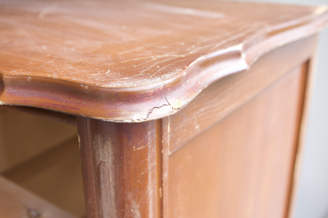 Close-up of crack on edge of wooden dresser.