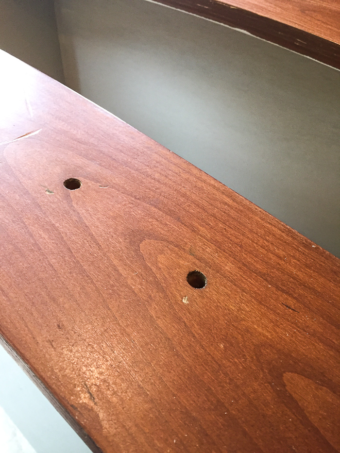Close-up of two holes drilled in furniture drawer.