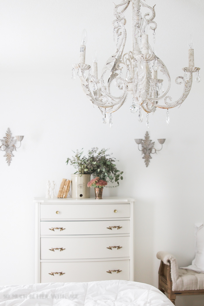 8 Steps on How to Finish Badly Damaged Furniture / white painted dresser with white chandelier in bedroom - So Much Better With Age