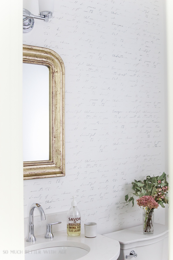 French script stencilled wall in bathroom with gold mirror and silhouette artwork