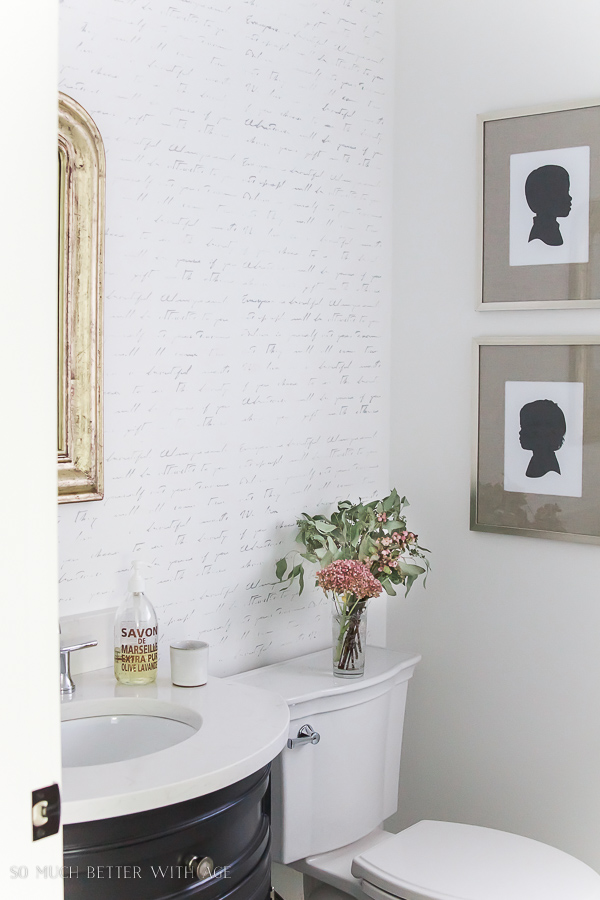 French script stencilled wall in bathroom with gold mirror and silhouette artwork - So Much Better With Age