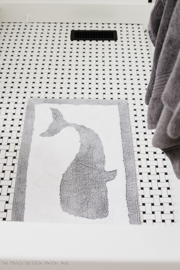 Simple clean and white kids bathroom reveal / Black and white basketweave tile bathroom floor with whale  bathroom mat - So Much Better With Age