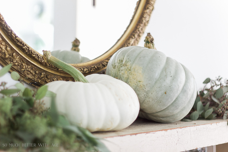 Heirloom pumpkins with gold mirror in French country dining room